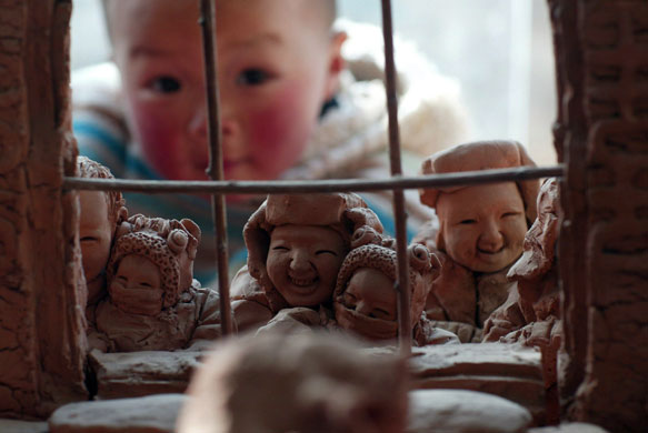 Yangjitun, China: A child looks at a set of clay figures made by a villager. Photograph: San Lang/EPA